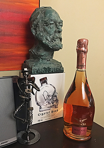 A bottle of pink wine sits on a table in front of a green bust of a man.