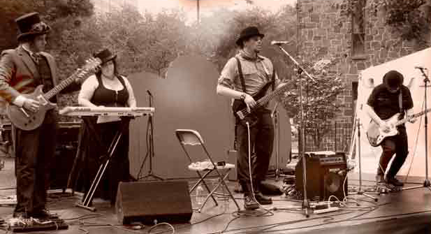 A sepia toned photo of four people in steampunk costume performing music on an outdoor stage.